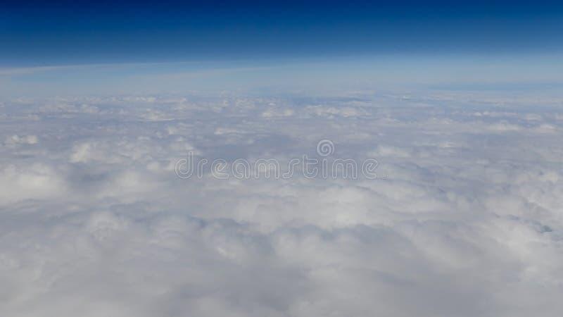 Mooie cloudscape met duidelijke blauwe hemel Een mening van vliegtuigvenster stock afbeelding