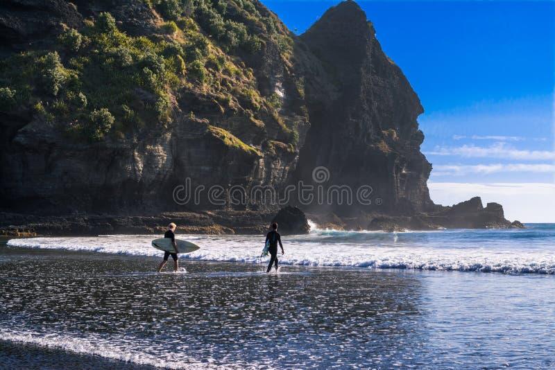 Mooie dag bij Piha-strand Jonge surfers die in water leiden royalty-vrije stock fotografie