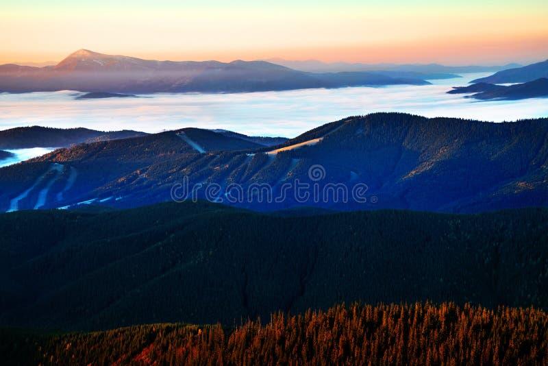 Mooie dageraad in de bergketen Bergen in mist in een toneellandschapsmening die worden gehuld Plaats Karpatische bergen royalty-vrije stock foto's
