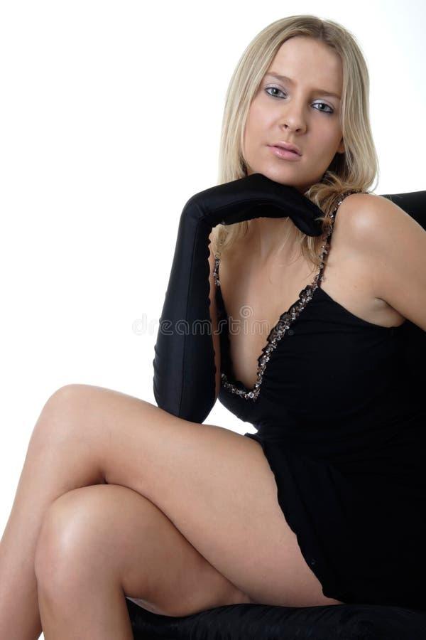Mooie dame in de zitting van de cocktailkleding op zwarte stoel royalty-vrije stock foto's