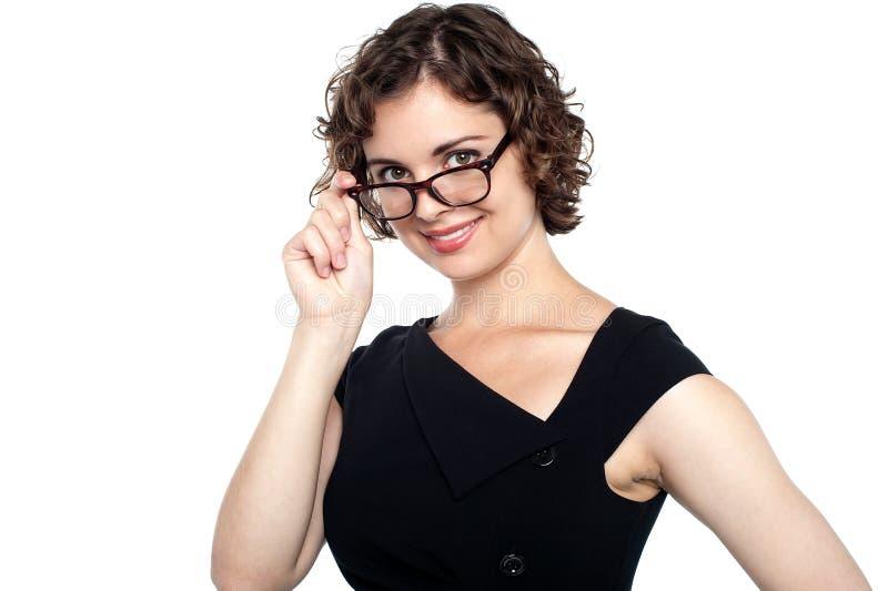 Mooie dame die haar oogglazen aanpassen stock fotografie