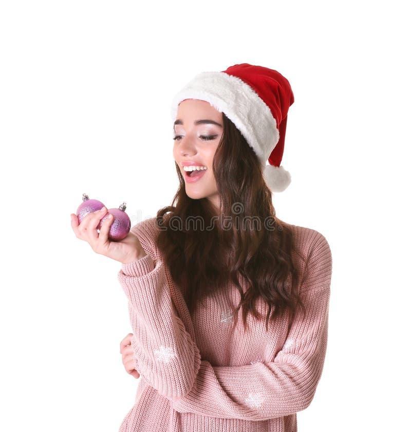 Mooie dame die in Kerstmishoed glanzende snuisterijen houden stock afbeeldingen