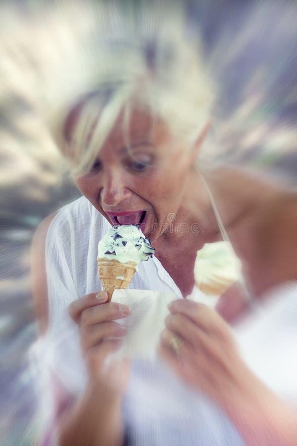 Mooie dame die roomijszitting op een deckchair eten royalty-vrije stock afbeeldingen