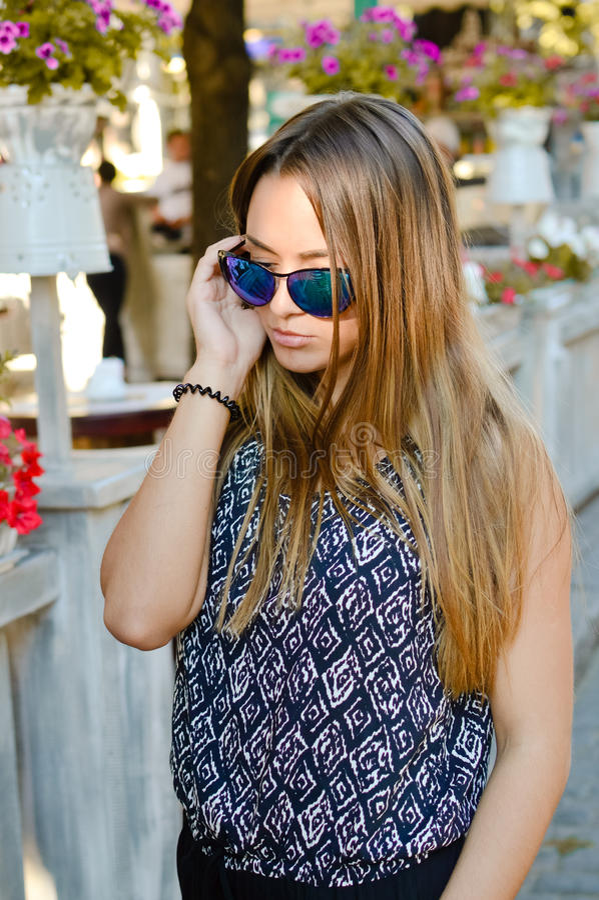 Mooie dame die zonnebril dragen die telefonisch spreken stock fotografie