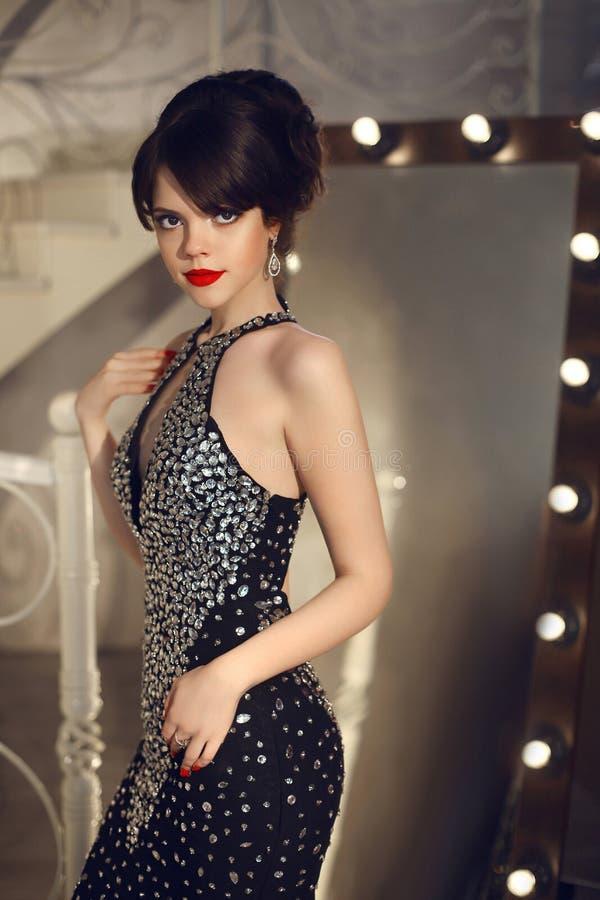 Mooie dame in manierkleding het stellen door spiegel met gloeilamp royalty-vrije stock foto