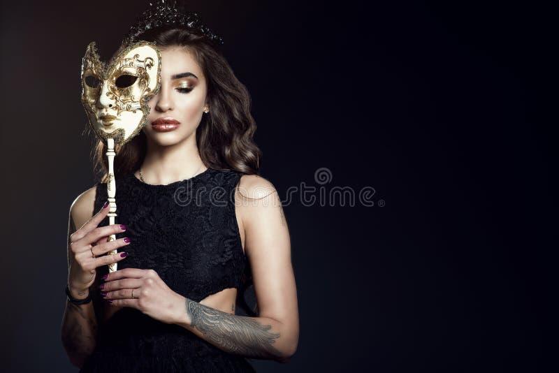 Mooie dame met gesloten ogen die de helft van haar gezicht achter het Venetiaanse masker verbergen stock foto's