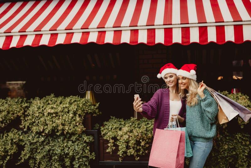 Mooie dame op middelbare leeftijd en haar dochter die in santahoeden selfie maken royalty-vrije stock afbeeldingen