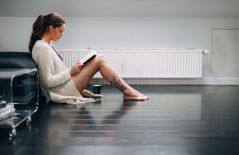 Mooie dame op vloer die thuis een roman lezen stock afbeeldingen