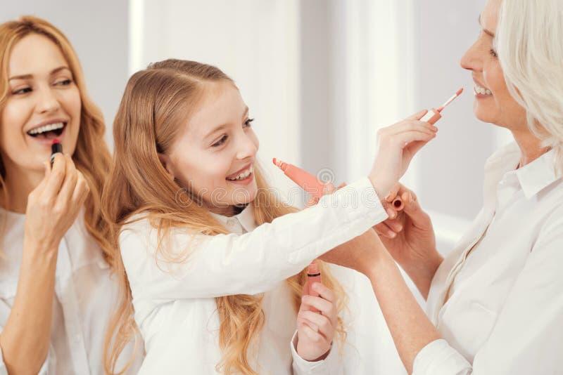 Mooie dames die van verschillende leeftijd lippenmake-up samen toepassen royalty-vrije stock foto's