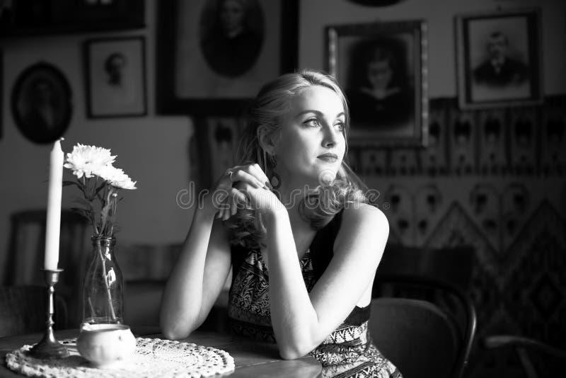 Mooie damezitting bij een lijst, een zwart-wit portret in retro stijl royalty-vrije stock fotografie