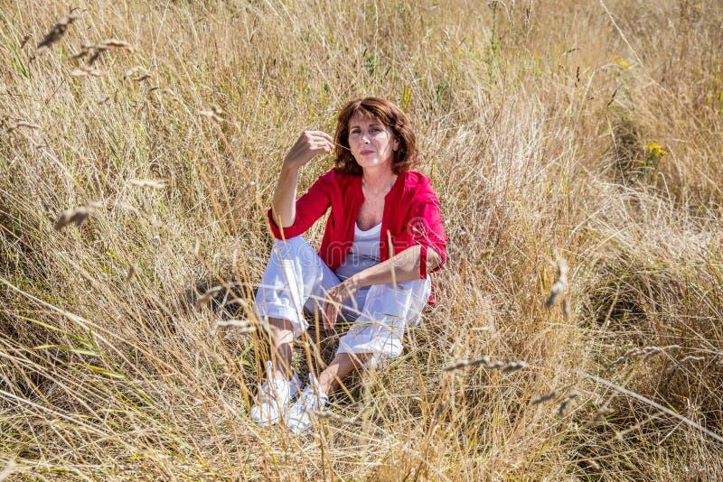 Mooie damezitting op hoog droog de zomergebied om van zon te genieten stock fotografie