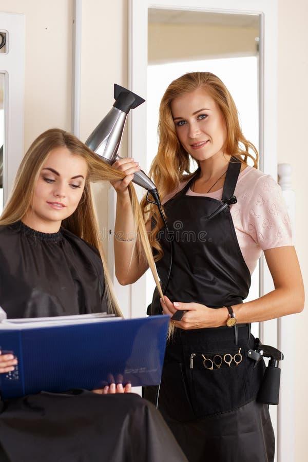 Mooie de holdingskam van de blonde vrouwelijke kapper en hairdryer royalty-vrije stock afbeelding
