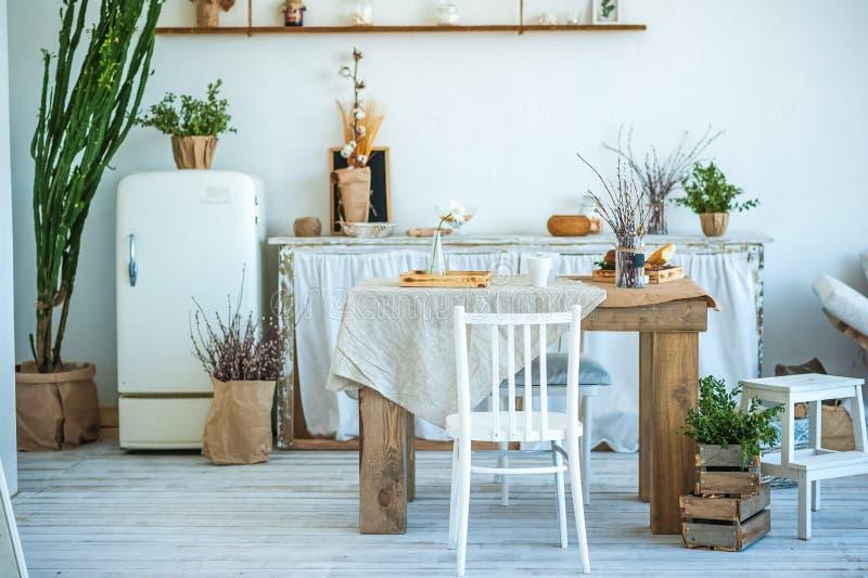Mooie de lentefoto van keukenbinnenland in lichte geweven kleuren Keuken, woonkamer met beige bankbank, oud retro wit Fr stock afbeeldingen