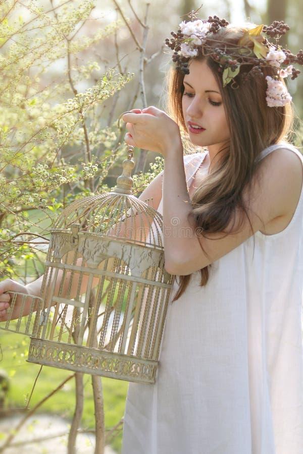 Mooie de lentenimf die een uitstekende vogelkooi openen stock foto