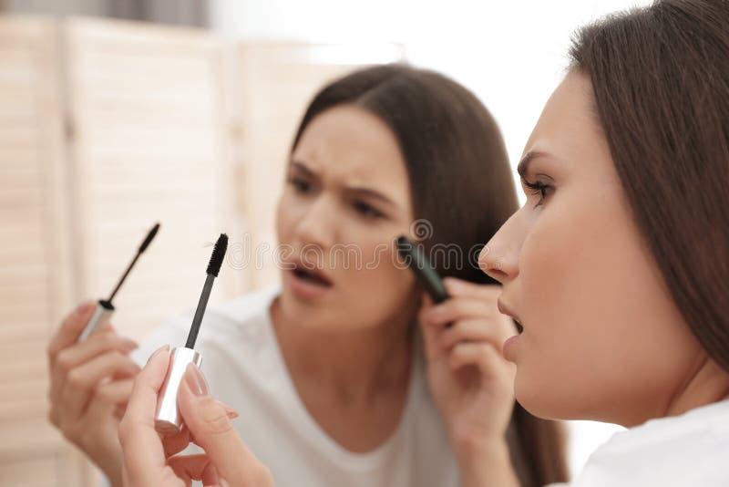 Mooie de mascaraborstel van de vrouwenholding met gevallen wimpers dichtbij spiegel stock fotografie