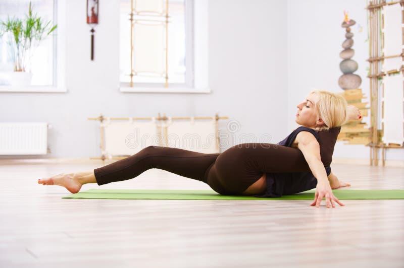 Mooie de praktijkenyoga van de yogivrouw het liggen padasirsasana van asanaeka - één been achter hoofd stelt in de geschiktheidsr stock afbeelding