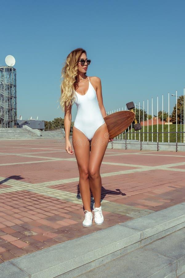 Mooie de vleetraad van het vrouwen lange haar, longboard, de meisjeszomer in stad De witte bodysuit tennisschoenen van zwempakgla royalty-vrije stock afbeeldingen