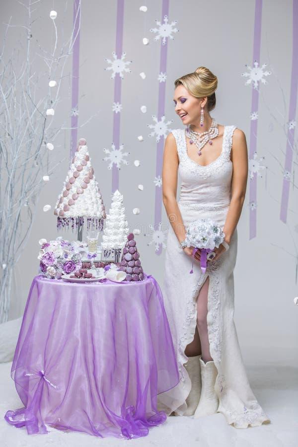 Mooie de winterbruid met huwelijkscake stock fotografie