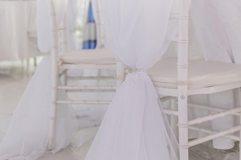 Mooie decoratie van de huwelijkspartij, witte stof op de stoelen stock foto's