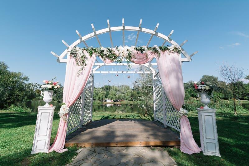 Mooie decoratie voor de ceremonie van het de zomerhuwelijk in openlucht Huwelijksboog die van lichte doek en witte en roze bloeme royalty-vrije stock fotografie