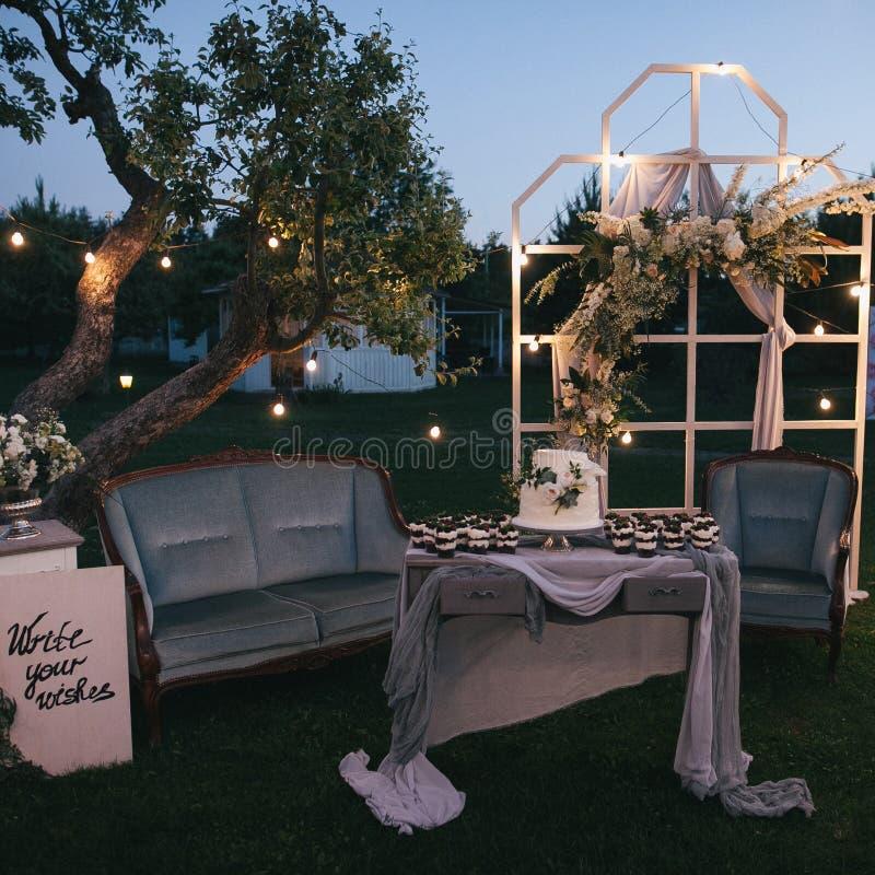 mooie decoratieve verlichte huwelijksboog en cake met desserts stock afbeelding