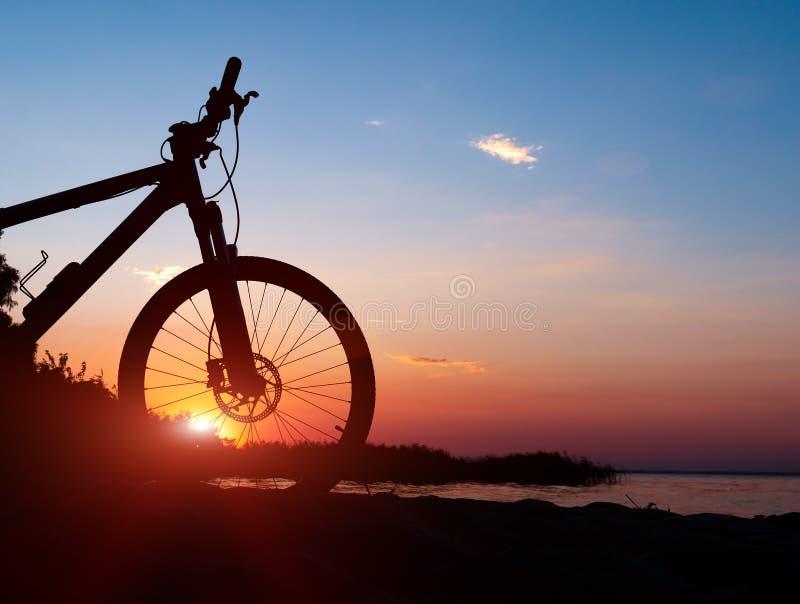 Mooie dichte omhooggaande scène van fiets bij zonsondergang, zon op blauwe hemel met uitstekende kleuren, silhouet van fiets voor royalty-vrije stock afbeeldingen