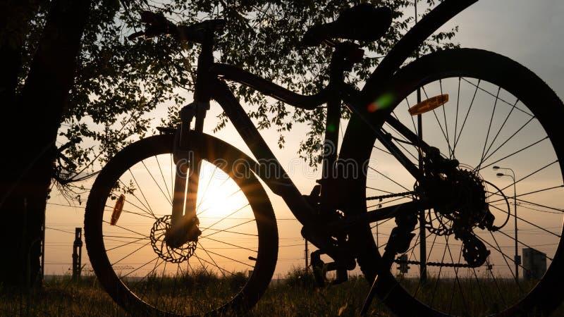 Mooie dichte omhooggaande sc?ne van fiets bij zonsondergang, zon op blauwe hemel met uitstekende kleuren, silhouet van fiets voor royalty-vrije stock foto