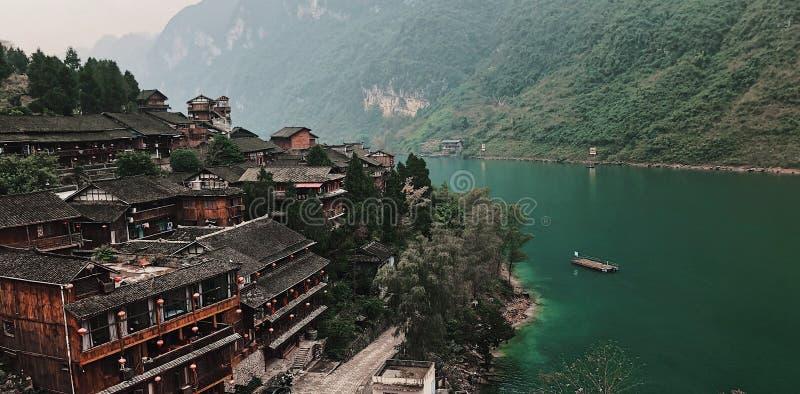 Mooie die antenne van een klein dorp in China met een meer en heuvels aan de kant op een mistige dag wordt geschoten royalty-vrije stock afbeelding