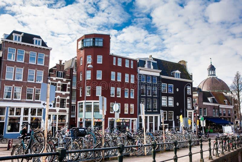 Mooie die architectuur en partijen van fietsen bij het Oude Centrale district in Amsterdam worden geparkeerd royalty-vrije stock afbeeldingen