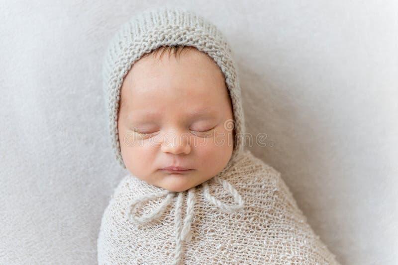 Mooie die babyslaap in een omslag, close-up wordt ingewikkeld stock foto