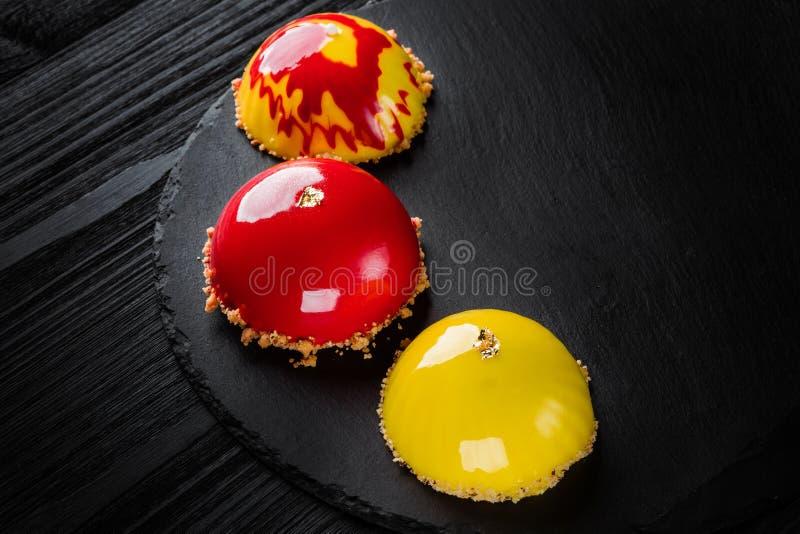 Mooie die cakes met glanzende rode en gele glans worden behandeld De desserts van het conceptontwerpgebakje stock fotografie