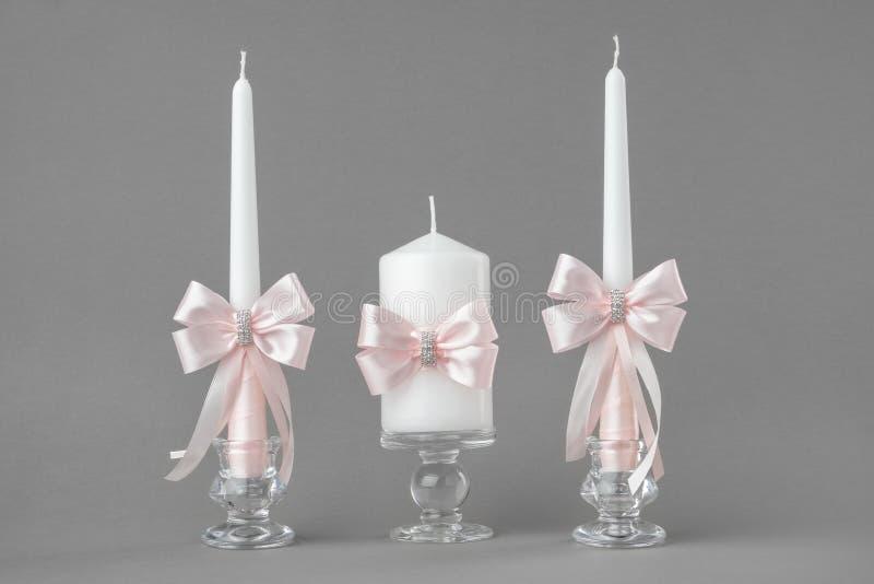Mooie die kaarsen met roze bogen worden verfraaid stock fotografie