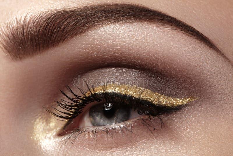Mooie die macro van vrouwelijk oog met plechtige make-up wordt geschoten Perfecte vorm van wenkbrauwen, eyeliner en vrij gouden l royalty-vrije stock foto