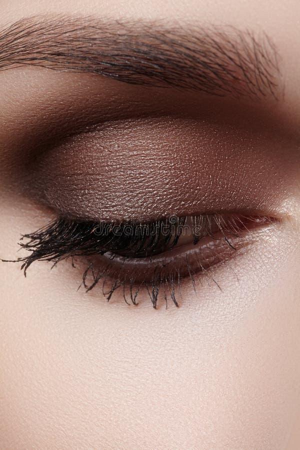 Mooie die macro van vrouwelijk oog met rokerige make-up wordt geschoten Perfecte vorm van wenkbrauwen royalty-vrije stock afbeeldingen