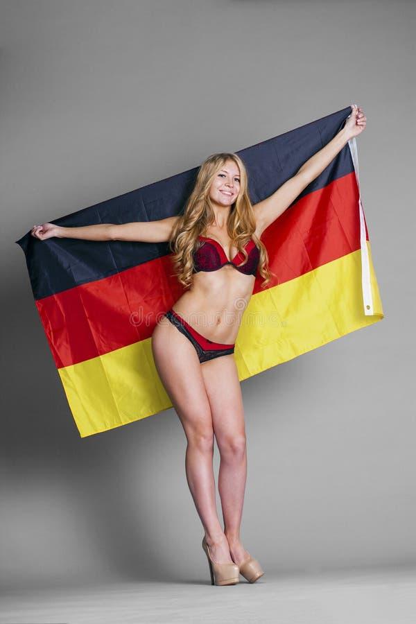Mooie die vrouw in de Duitse vlag wordt verpakt stock foto