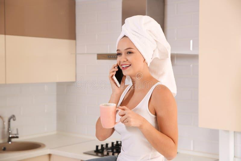 Mooie die vrouw met hoofd in handdoek het drinken thee wordt verpakt en het spreken op telefoon stock fotografie