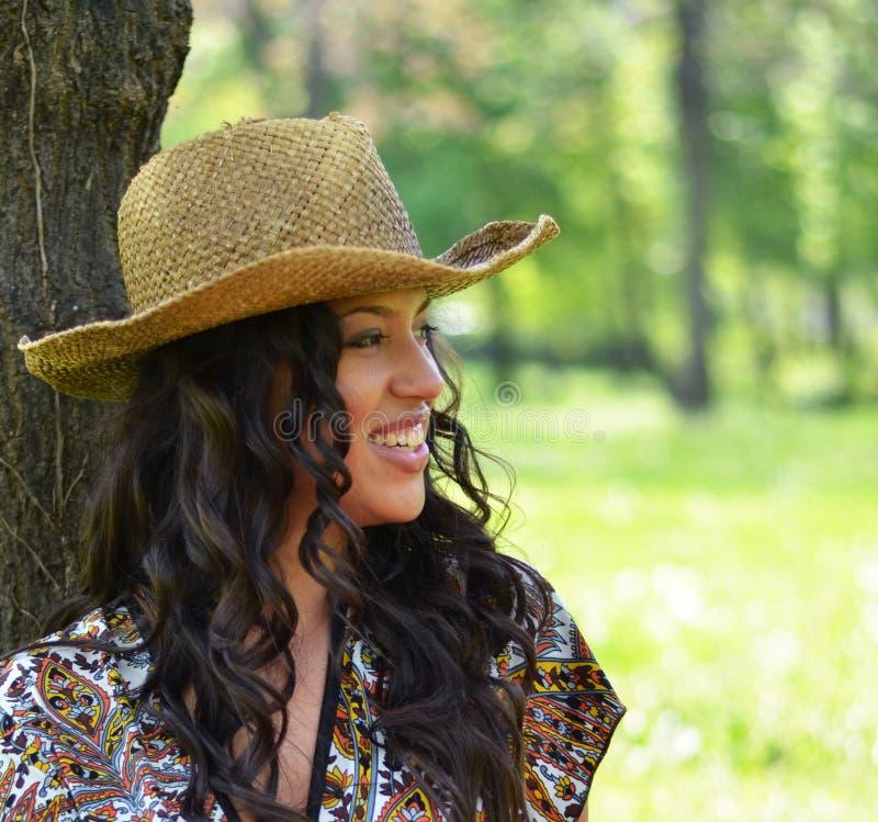 Mooie die vrouw met strohoed tegen boom wordt geleund royalty-vrije stock foto's