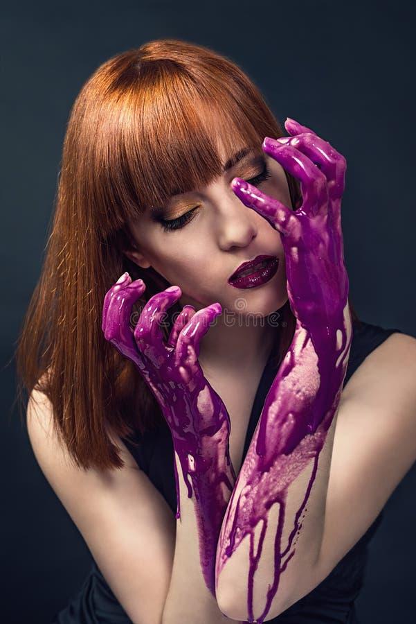 Mooie die vrouw met vingers in verf worden behandeld stock afbeelding