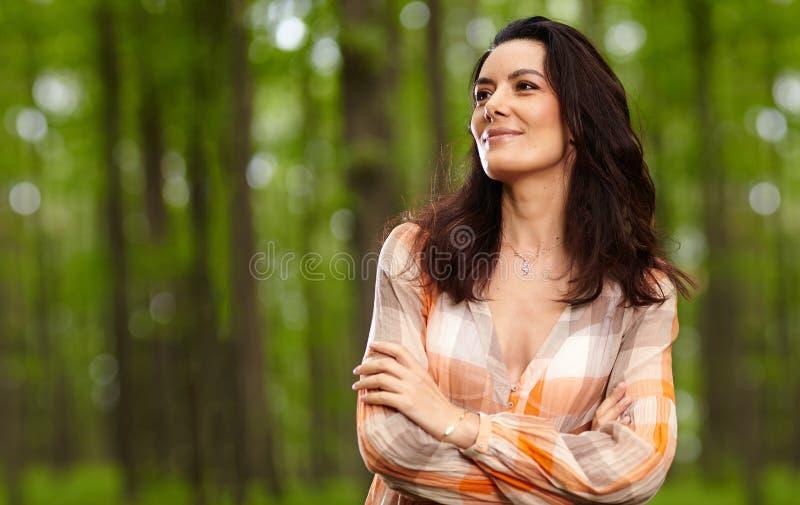 Mooie die vrouw met wapens in een bos worden gevouwen stock fotografie