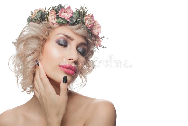 Mooie die vrouw op wit, portret wordt geïsoleerd Mooi model met make-up, blonde krullende haar en bloemen stock fotografie