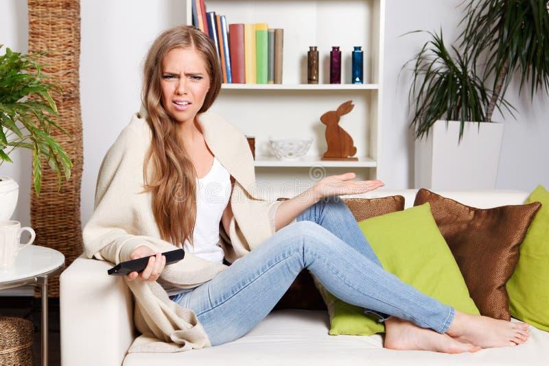 Mooie die vrouw over het letten op TV wordt verstoord stock foto