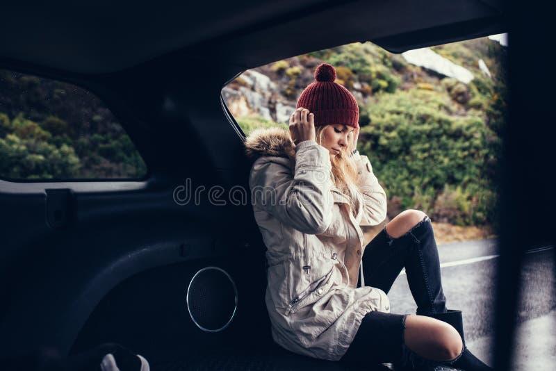 Mooie die vrouwenzitting in autoboomstam wordt ontspannen stock foto's