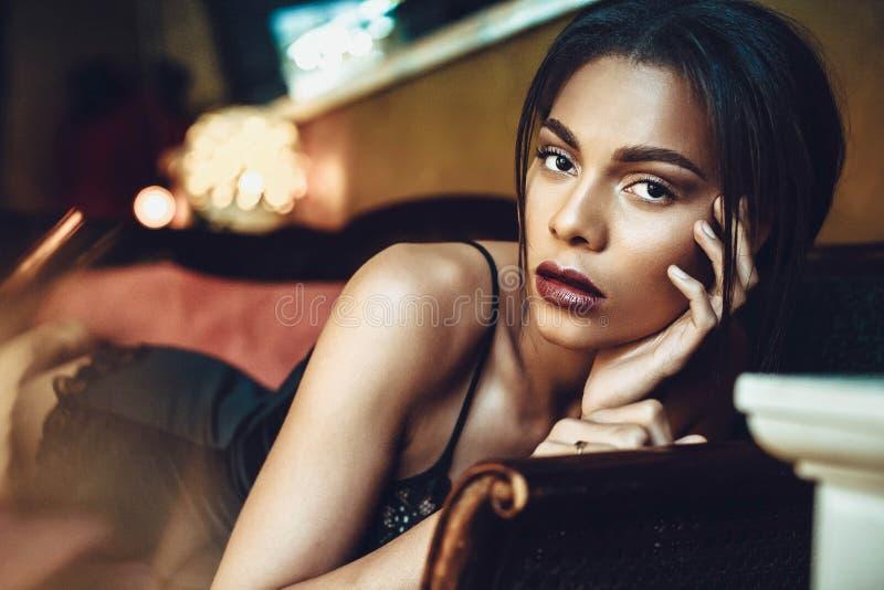 Mooie donker-gevilde jonge vrouw die sensualy in zwarte lingerie stellen Manier photoshoot stock afbeelding