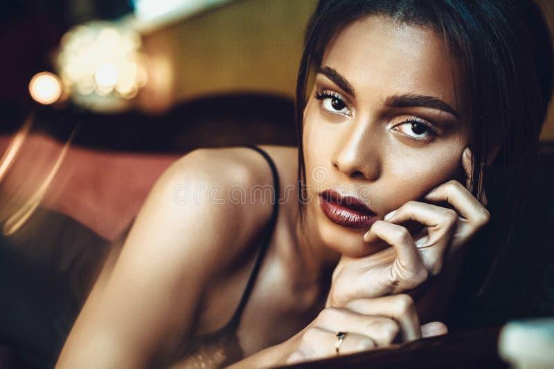 Mooie donker-gevilde jonge vrouw die sensualy in zwarte lingerie stellen Manier photoshoot stock foto's