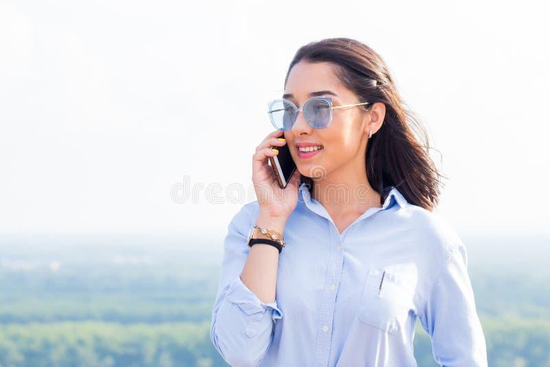 Mooie donkerbruine bedrijfsvrouw die gelukkig op een smartphone in aard in de zomer spreken royalty-vrije stock afbeeldingen