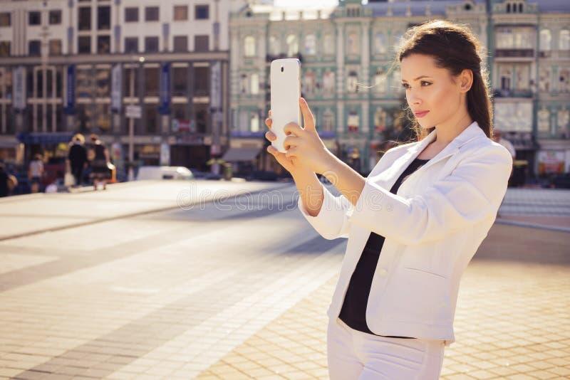 Mooie donkerbruine bedrijfsvrouw in wit kostuum die fotograferen stock foto's