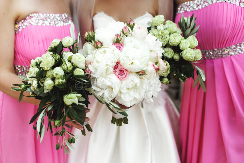 Mooie donkerbruine bruid en schitterende bruidsmeisjes met boeketten stock fotografie