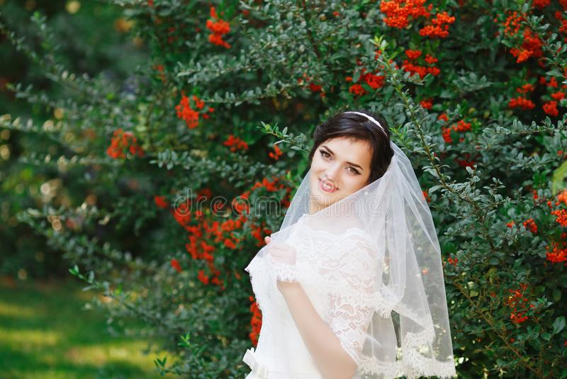 Mooie donkerbruine bruid met boeket openlucht De gelukkige bruid overtreft royalty-vrije stock foto