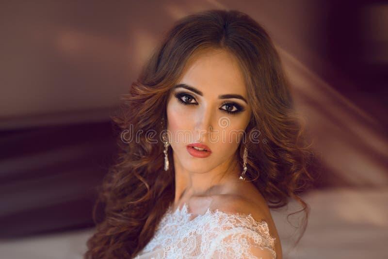 Mooie donkerbruine bruid met ceremoniesamenstelling en krullend haar stock foto