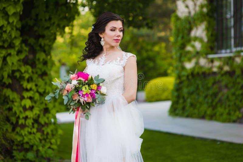 Mooie donkerbruine bruid met sluier en boeket royalty-vrije stock afbeeldingen
